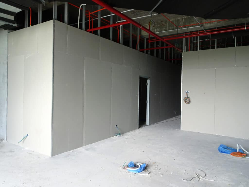 Drywall installation work in progress by construction workers at the construction site. It is the easiest and cheapest way to do partition for interior wall.